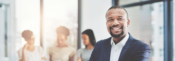 African-american male business partner smiling in his corporate office
