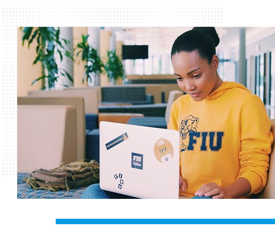 young woman with hair in a bun, wearing FIU sweatshirt, working on her laptop